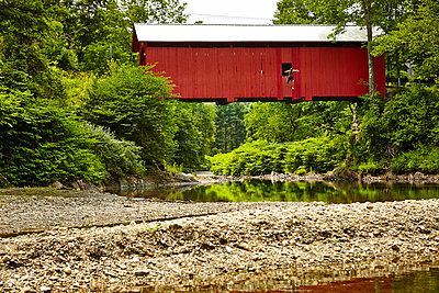 A man leaps from a Vermont covered bridge.  - p343m1203844 by Josh Campbell