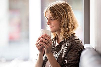 Junge Frau trinkt einen Becher Kaffee - p788m1466104 von Lisa Krechting