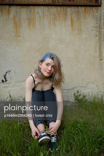 Junge Frau sitzt im Gras vor einer Mauer - p1646m2264265 von Slava Chistyakov