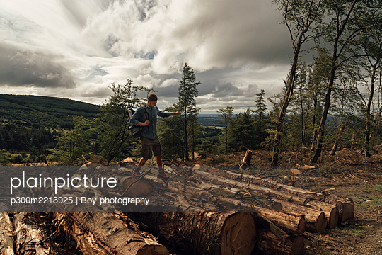 Male hiker walking on logs against cloudy sky in forest - p300m2213925 by Boy photography