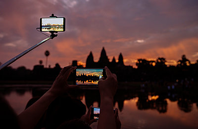 Cropped image of tourists photographing silhouette Angkor Wat temple during sunset - p1166m1150959 by Cavan Images