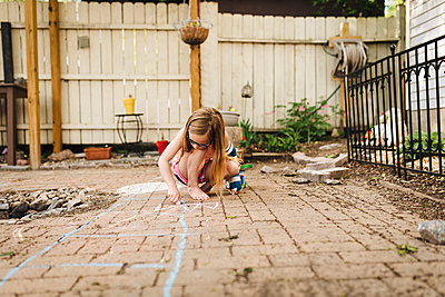 Little girl wearing arm cast draws on patio with sidewalk chalk - p1166m2106898 by Cavan Images