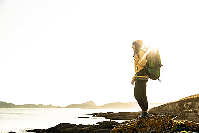 Woman exploring the coastline with backpack - p1166m2193742 by Cavan Images