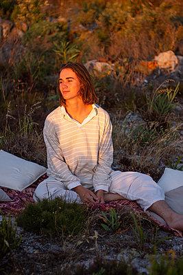 Teenage boy sits on blanket in a meadow - p1640m2245949 by Holly & John