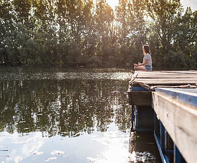 Relaxed woman sitting on jetty at a remote lake - p300m2114937 by Uwe Umstätter