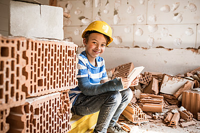 Smiling boy sitting with book at attic during renovation - p300m2287496 by Epiximages