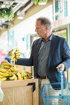 Mature man examining bananas in organic supermarket - p426m1407409 by Kentaroo Tryman