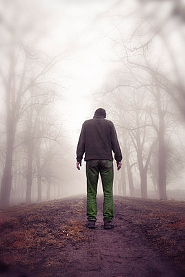 Rearview man standing on rural path in fog - p5970368 by Tim Robinson