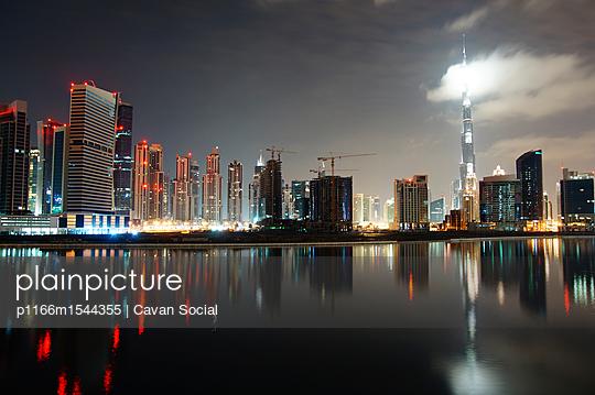 Low angle view of Burj Khalifa amidst illuminated city against sky - p1166m1544355 by Cavan Social