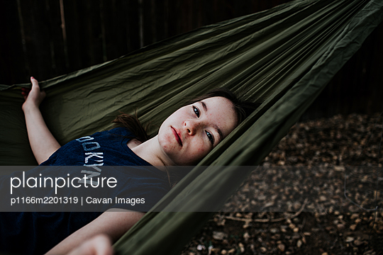 Preteen girl laying in hammock outside - p1166m2201319 by Cavan Images
