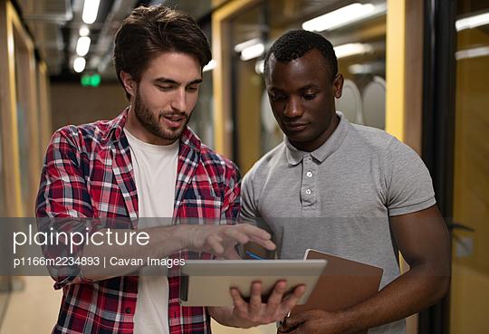 Diverse men using tablet in office corridor - p1166m2234893 by Cavan Images