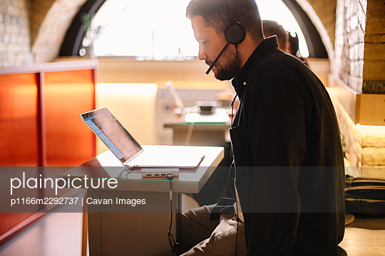 Man in headphones using laptop computer at cafe - p1166m2292737 by Cavan Images