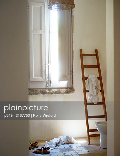 Ladder towel rack and sandals with dropped towels in Sicilian home - p349m2167750 by Polly Wreford
