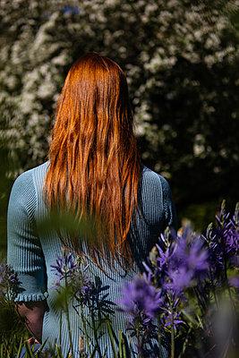 Rothaarige Frau sitzt auf Blumenwiese - p045m2082432 von Jasmin Sander