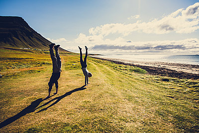 Father and daughter doing handstand, West fjords, Iceland - p1084m986841 by Operation XZ