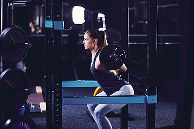 Young woman doing squads with barbell at fitness centre - p1166m2095469 by Cavan Images