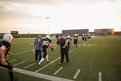 Coaches high-fiving teenage boy high school football team before game on football field - p1192m1500254 by Hero Images