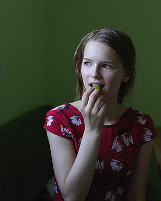 Young woman eating grape - p1376m2108542 by Melanie Haberkorn