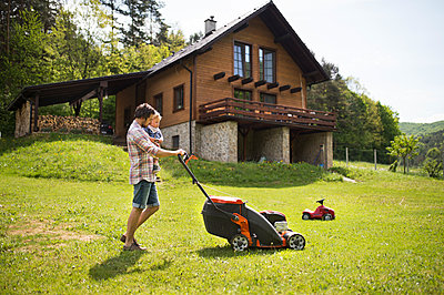 Father with his little son mowing the lawn - p300m2012589 by HalfPoint