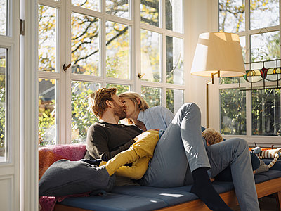 Couple kissing in sunroom at home with son lying on their lap - p300m2205499 by Kniel Synnatzschke