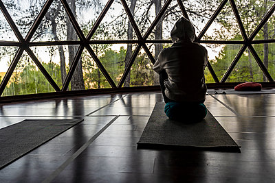 Male tourist wearing hood sitting on exercise mat at health retreat - p300m2225165 by Javier De La Torre Sebastian