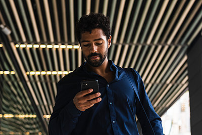Male business person using smart phone in city - p300m2226496 by NOVELLIMAGE