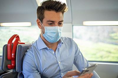 Businessman wearing face mask using smart phone while sitting in train - p300m2242869 by Ignacio Ferrándiz Roig
