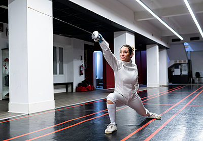 Womanin fencing outfit practicing at gym - p300m2243594 by Jose Carlos Ichiro