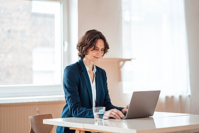 Mature businesswoman using laptop on table at home office - p300m2267055 by Robijn Page