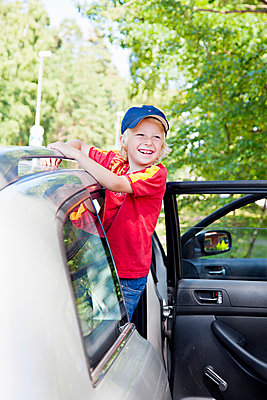 Boy looking from car - p312m1551911 by Johner Images