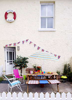 Pebble-dashed exterior of Isle of Wight home picnic table and Union Jack bunting - p349m790349 by Brent Darby