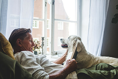 Senior man reading book while relaxing with dog on bed at home - p426m2046389 by Maskot