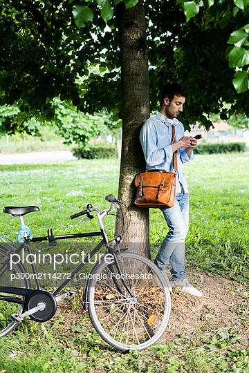 Young man with bicycle using smartphone, headphones around neck, standing under tree - p300m2114272 von Giorgio Fochesato