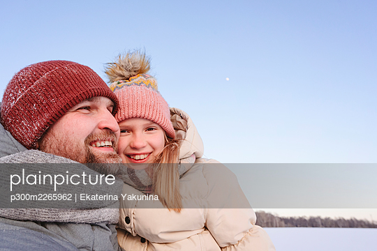 Cute daughter with smiling father against sky during winter - p300m2265962 by Ekaterina Yakunina