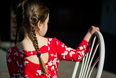 rear view of a little girl with long braids sitting in patch of light - p1166m2095273 by Cavan Images