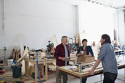 Carpenters talking at workbench in workshop - p1192m1490216 by Hero Images
