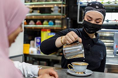 Waitress wearing bandana pouring milk in cup at coffee shop - p300m2281881 by Ignacio Ferrándiz Roig
