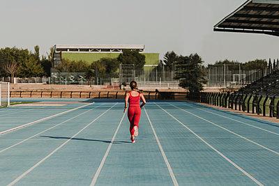 Active female athlete running on sports track at stadium - p300m2287438 by Eva Blanco