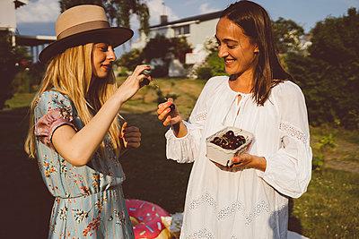 Beste Freundinnen essen Kirschen im Garten - p432m2260291 von mia takahara
