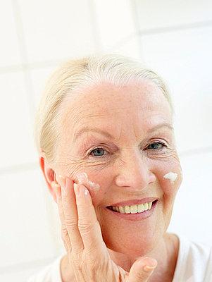 Aeltere Frau beim Eincremen  - p6430351f von senior images RF
