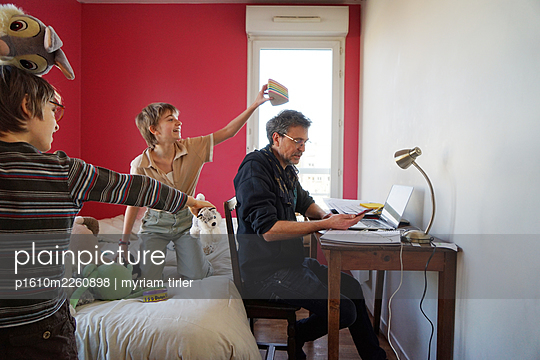 A man working at home with kids playing around - p1610m2260898 by myriam tirler