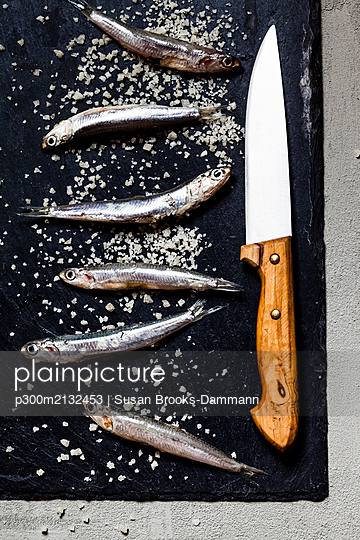 Close-up of fresh anchovies and sea salt with knife on slate rock - p300m2132453 by Susan Brooks-Dammann