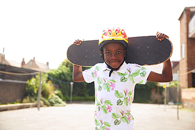 Portrait confident boy with skateboard in sunny parking lot - p1023m2238499 by Himalayan Pics