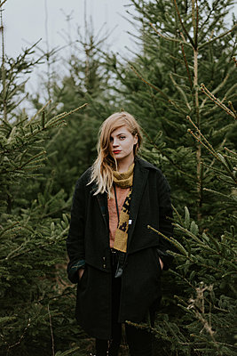 Young woman standing among fir trees - p1184m1222704 by brabanski