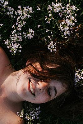 Teenager liegt auf dem Rücken auf einer Blumenwiese - p1507m2172044 von Emma Grann