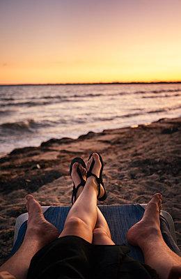Pärchen liegt auf einer Liege am Strand bei Sonnenuntergang - p1515m2101054 von Daniel K.B. Schmidt