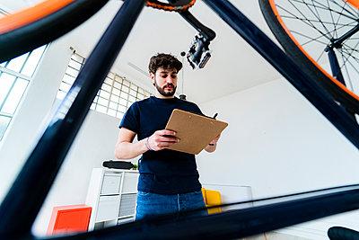 Man repairs a bicycle - p300m2275289 von Giorgio Fochesato