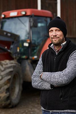 Farmer standing next to tractor - p312m2239798 by Plattform