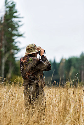 Teenager with binoculars watching forest - p312m798844 by Hans Berggren