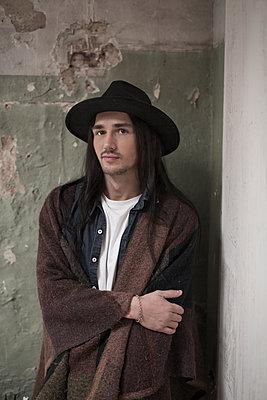 Junger Mann mit Hut und Poncho - p341m1218764 von Mikesch
